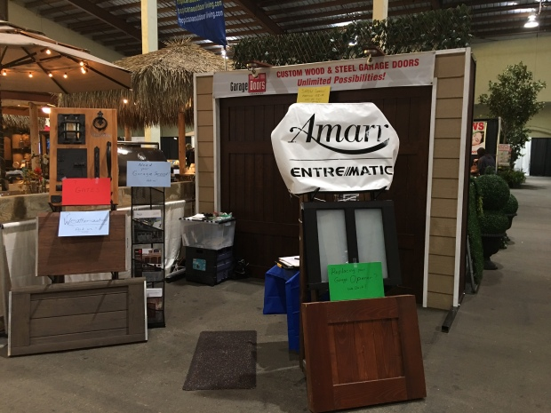 Trade show booth with wood garage door and Amarr Entrematic sign, garage door samples like steel, glass, faux-wood